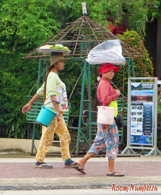 Девушки несут тазики на головах в Сиануквиле, Камбоджа