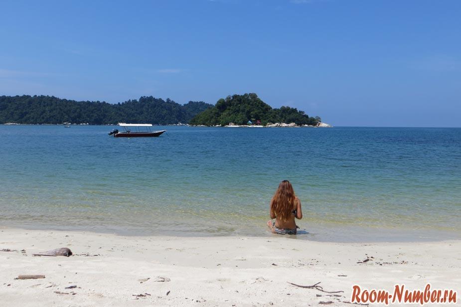 Девушка сидит на пляже и смотрит на море и необитаемый остров