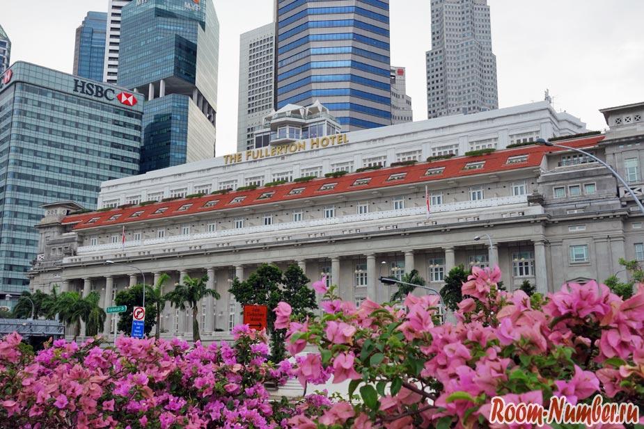 Отель в Сингапуре Фулертон вечером со стороны парка Мерлион и цветочной клумбы