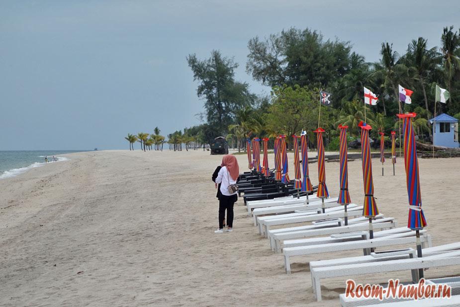 Девушка гуляет по пляжу возле шезлонгов
